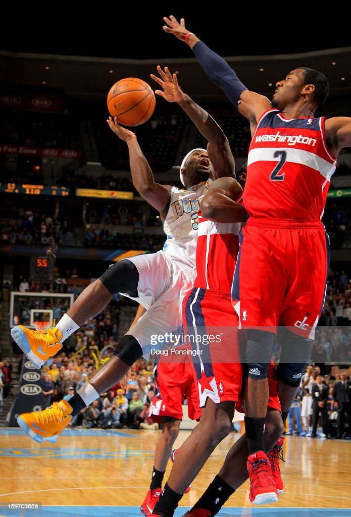 Ty Lawson #3 of the Denver Nuggets has his shot blocked by John Wall #2 of the Washington Wizards with 2.7 seconds remaining in the game at the Pepsi Center on January 18, 2013 in Denver, Colorado. The Wizards defeated the Nuggets 112-108.