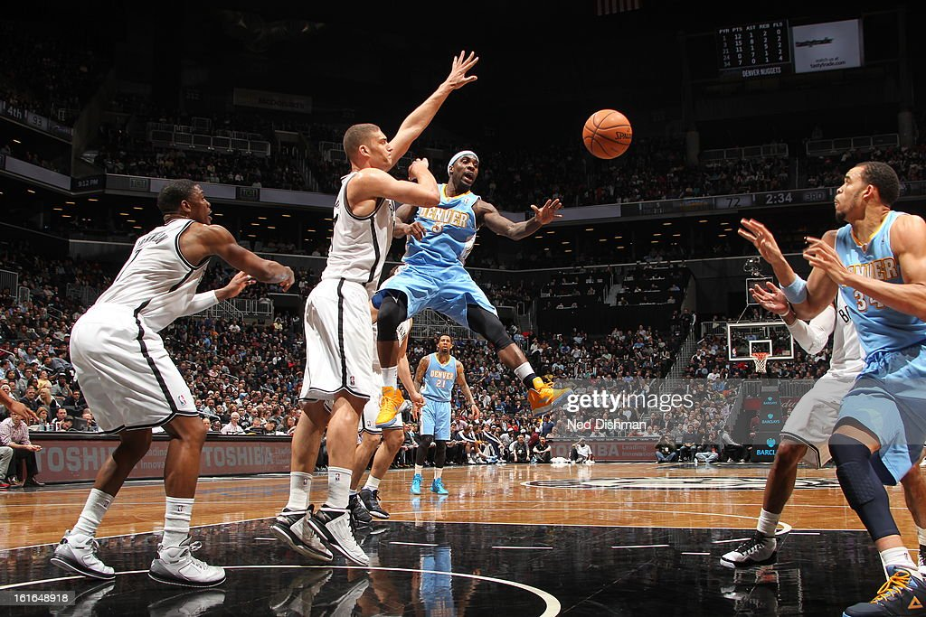 Ty Lawson #3 of the Denver Nuggets passes the ball down low against the Brooklyn Nets at the Barclays Center on February 13, 2013 in the Brooklyn borough of New York City in New York City.