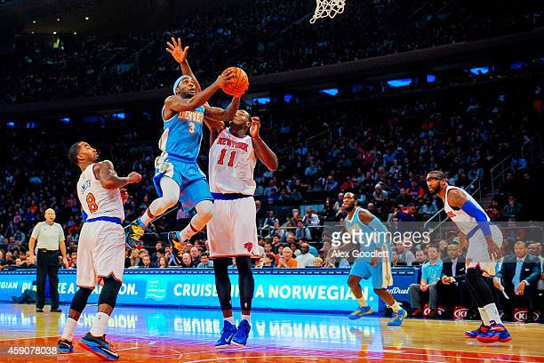 Ty Lawson of the Denver Nuggets shoots over Samuel Dalembert of the New York Knicks in the first half at Madison Square Garden on November 16 2014 in...