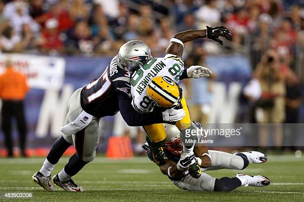 Ty Montgomery of the Green Bay Packers is tackled by Jordan Richards and Robert McClain of the New England Patriots in the third quarter during a...
