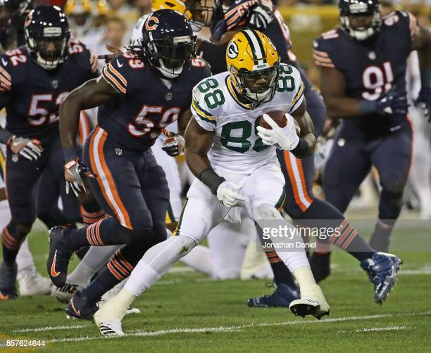 Ty Montgomery of the Green Bay Packers runs past Danny Trevathan of the Chicago Bears at Lambeau Field on September 28 2017 in Green Bay Wisconsin...