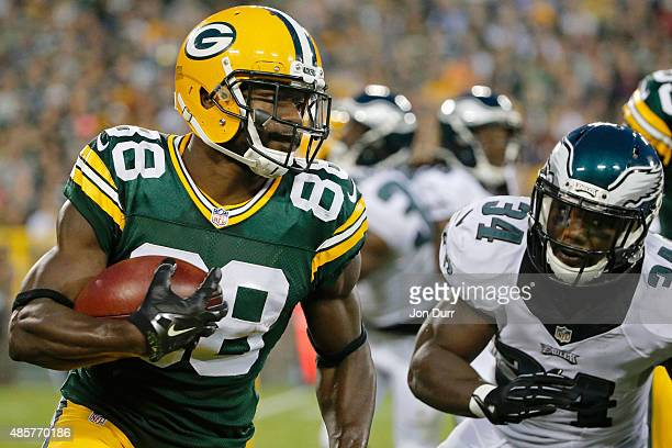 Ty Montgomery of the Green Bay Packers rushes as Kenjon Barner of the Philadelphia Eagles defends during a preseason game at Lambeau Field on August...