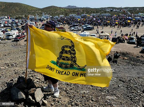Ty Park of Nevada puts up a flag on a hill overlooking the Tea Party Express' 'Showdown in Searchlight' rally March 27 2010 in Searchlight Nevada The...