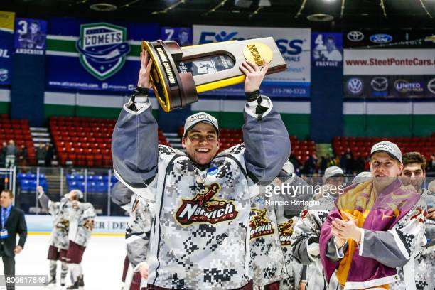 Ty Reichenbach of Norwich University celebrates with the championship trophy during the Division lll Men's Ice Hockey Championship held at the Utica...
