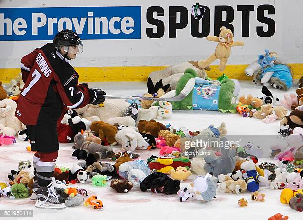 Ty Ronning of the Vancouver Giants helps pick up stuffed animals that were thrown on the ice after scoring a goal against the Everett Silvertips...