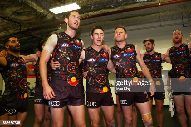 Ty Vickery James Cousins and Dallas Willsmore of the Hawks celebrate victory with team mates and sing the team song after the round 10 AFL match...