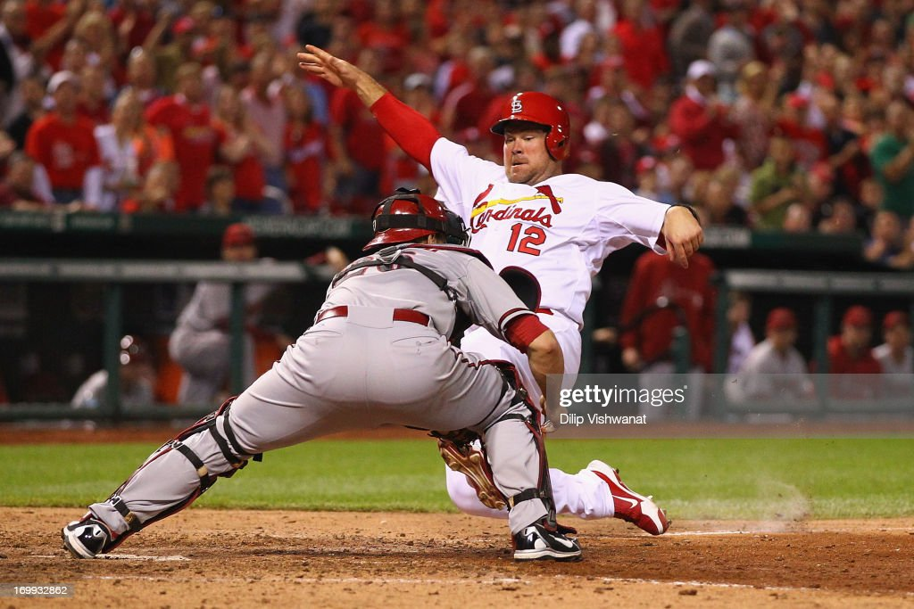 Ty Wigginton of the St Louis Cardinals slides safely into home against Miguel Montero of the Arizona Diamondbacks in the seventh inning at Busch...