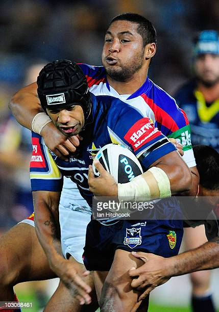 Ty Williams of the Cowboys is tackled by Con Mika of the Knights during the round 20 NRL match between the North Queensland Cowboys and the Newcastle...
