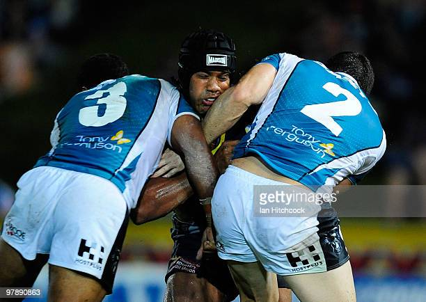 Ty Williams of the Cowboys is tackled by Michael Jennings and Michael Gordon of the Panthers during the round two NRL match between the North...