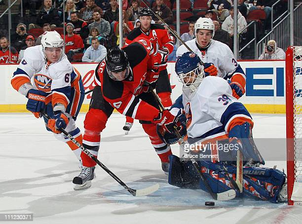 Ty Wishart and goaltender Rick DiPietro of the New York Islanders defend against Travis Zajac of the New Jersey Devils at the Prudential Center on...