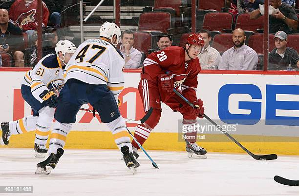 Tye McGinn of the Arizona Coyotes looks to pass the puck in front of Andre Benoit and Zach Bogosian of the Buffalo Sabres during the first period at...