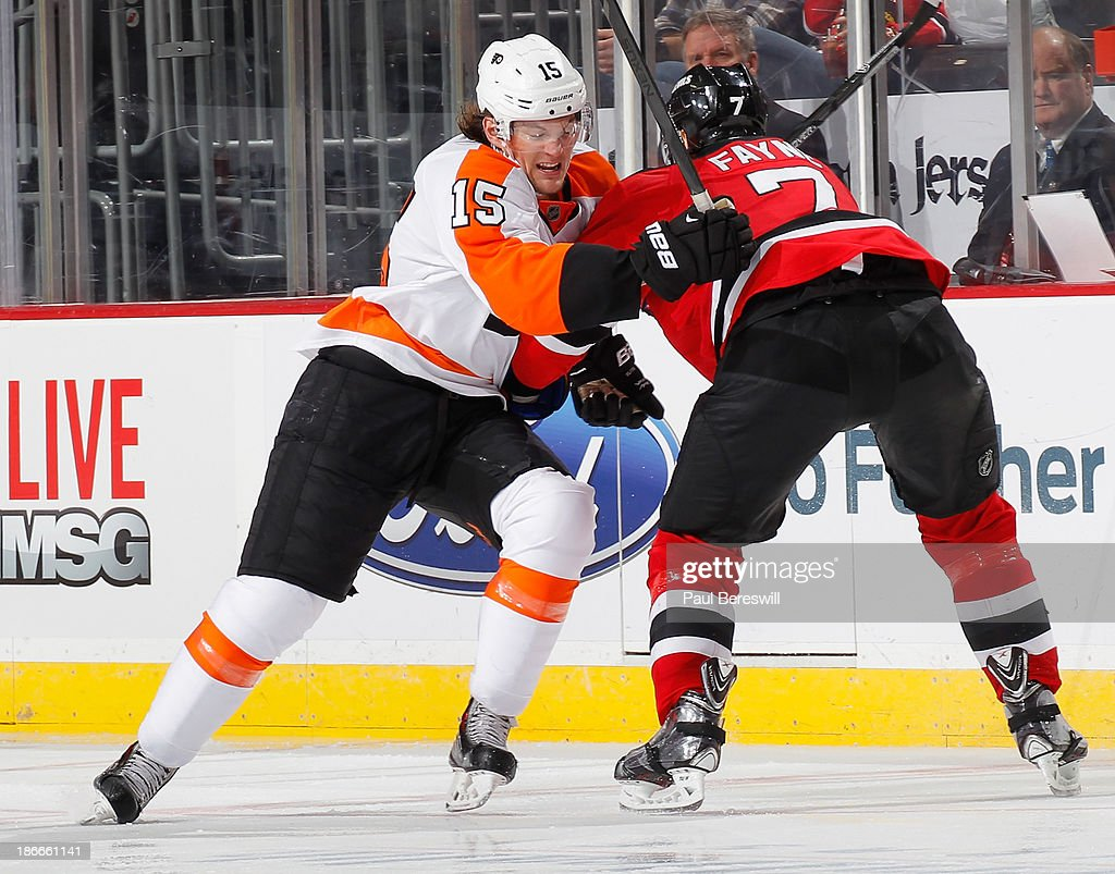 Tye McGinn #15 of the Philadelphia Flyers is stopped by Mark Fayne #7 of the New Jersey Devils during the third period of an NHL hockey game at Prudential Center on November 2, 2013 in Newark, New Jersey.