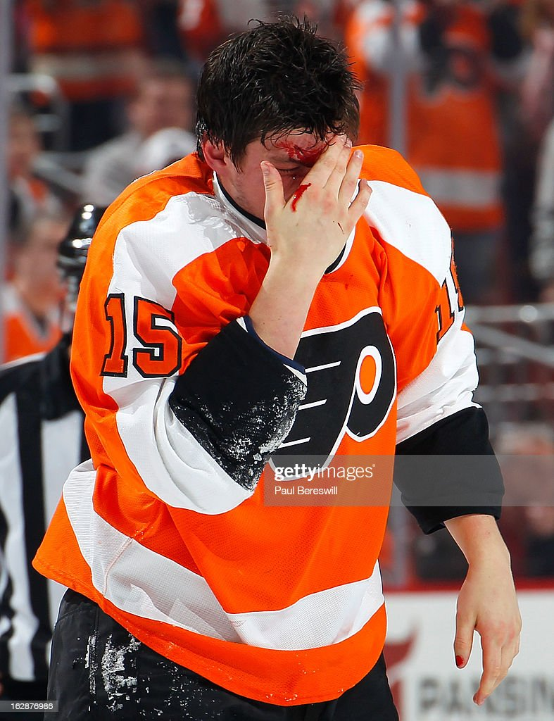 Tye McGinn #15 of the Philadelphia Flyers skates off the ice holdintg his head as he bleeds after a fight on the ice in an NHL Hockey game against the Toronto Maple Leafs at Wells Fargo Center on February 25, 2013 in Philadelphia, Pennsylvania.