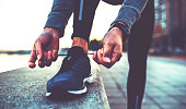Tying sports shoes. Sportsman getting ready for athletic and fitness training outdoors. Sport, exercise, fitness, workout. Healthy lifestyle