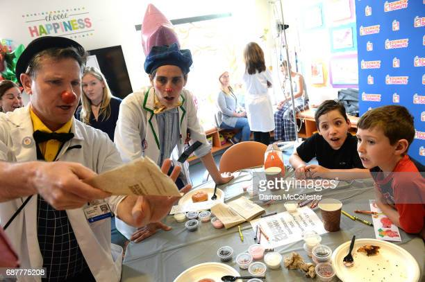 Tyler and Andrew watch the clowns during Dunkin' Donuts Iced Coffee Day benefitting Boston Children's Hospital at Boston Children's Hospital May 24...