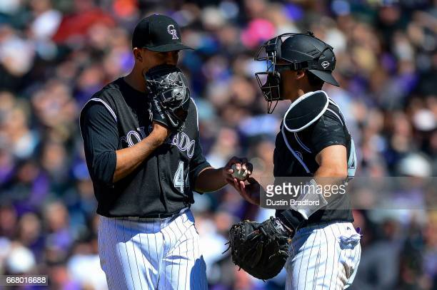 Tyler Anderson of the Colorado Rockies and Tony Wolters meet on the mound in the fifth inning of a game against the Los Angeles Dodgers at Coors...