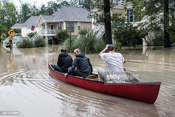 Tyler Bahnmuller Will Brennan and Matt Talley take a canoe to investigate their homes following flooding in the area October 5 2015 in Columbia South...