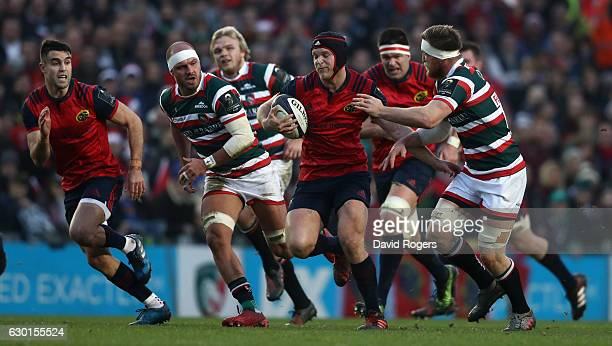 Tyler Bleyendaal of Munster is held by Brendon O'Connor during the European Rugby Champions Cup match between Leicester Tigers and Munster at Welford...