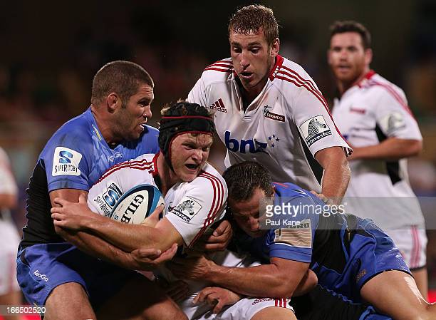 Tyler Bleyendaal of the Crusaders gets tackled by Matt Hodgson and Heath Tessmann of the Force during the round 9 Super Rugby match between the...