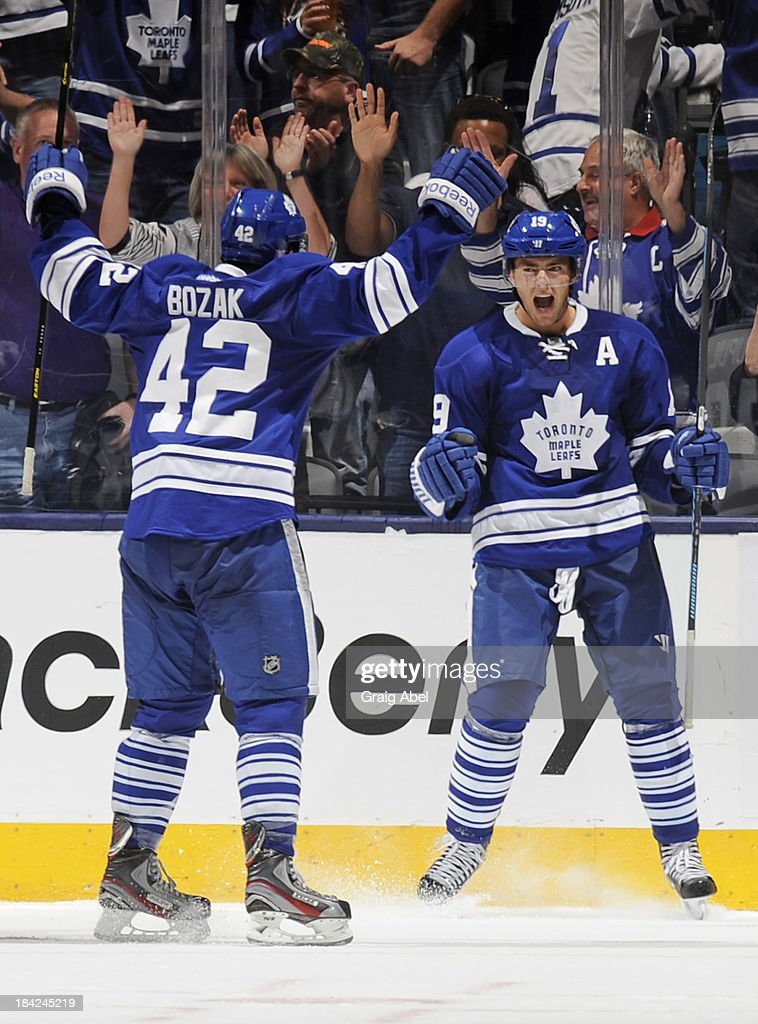 Tyler Bozak #42 and Joffrey Lupul #19 of the Toronto Maple Leafs celebrate the tying goal during NHL game action against the Edmonton Oilers October 12, 2013 at Air Canada Centre in Toronto, Ontario, Canada.