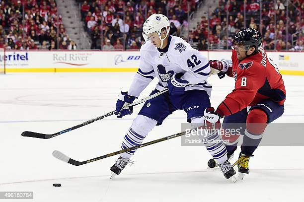 Tyler Bozak of the Toronto Maple Leafs and Alex Ovechkin of the Washington Capitals battle for the puck in overtime during an NHL game at Verizon...