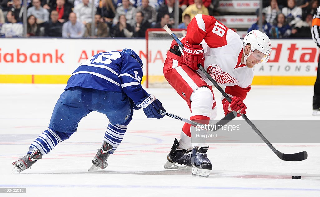 Tyler Bozak of the Toronto Maple Leafs battles for the puck with Joakim Andersson of the Detroit Red Wings during NHL game action December 13 2014 at...