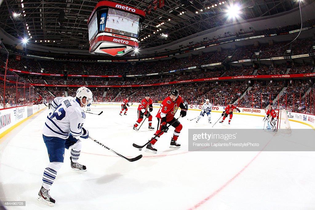 Tyler Bozak #42 of the Toronto Maple Leafs passes the puck against Cody Ceci #5 of the Ottawa Senators on April 12, 2014 at Canadian Tire Centre in Ottawa, Ontario, Canada.