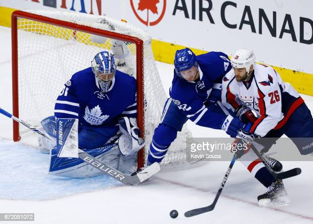 Tyler Bozak of the Toronto Maple Leafs prevents a wraparound attempt on his goaltender Frederik Andersen by Daniel Winnik of the Washington Capitals...