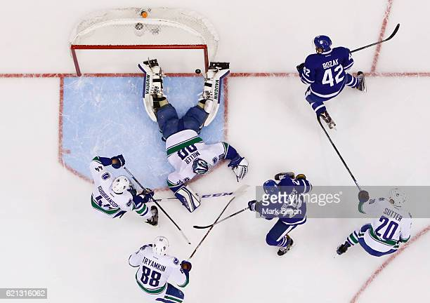 Tyler Bozak of the Toronto Maple Leafs scores on Ryan Miller of the Vancouver Canucks sprawls on the ice surrounded by teammates Erik Gudbranson...