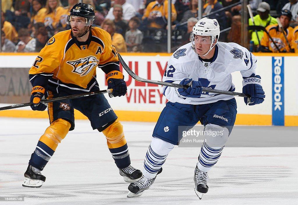 Tyler Bozak #42 of the Toronto Maple Leafs skates against Mike Fisher #12 of the Nashville Predators at Bridgestone Arena on October 10, 2013 in Nashville, Tennessee.