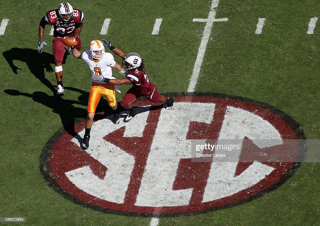 Tyler Bray of the Tennessee Volunteers chased by teammates Stephon Gilmore and Cliff Matthews of the South Carolina Gamecocks during their game at...