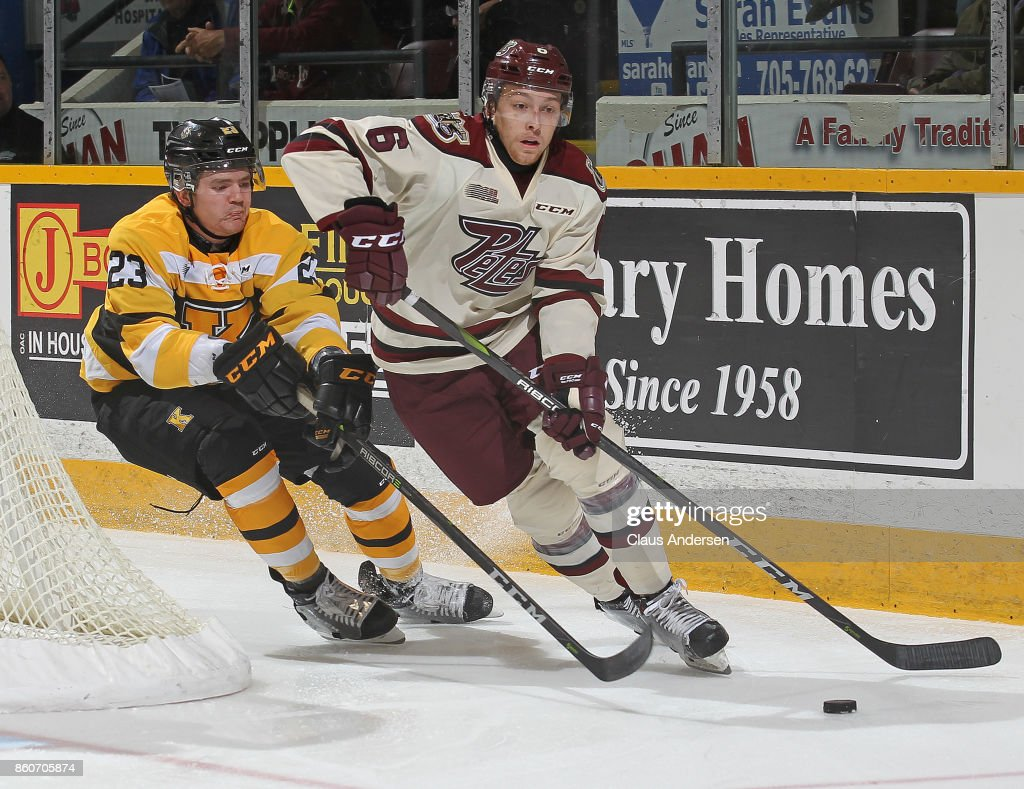 Tyler Burnie #23 of the Kingston Frontenacs skates to check Austin Osmanski #6 of the Peterborough Petes in an OHL game at the Peterborough Memorial Centre on October 12, 2017 in Peterborough, Ontario.