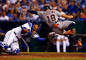 Tyler Collins of the Detroit Tigers is tagged out at home plate by Salvador Perez of the Kansas City Royals during the game at Kauffman Stadium on...