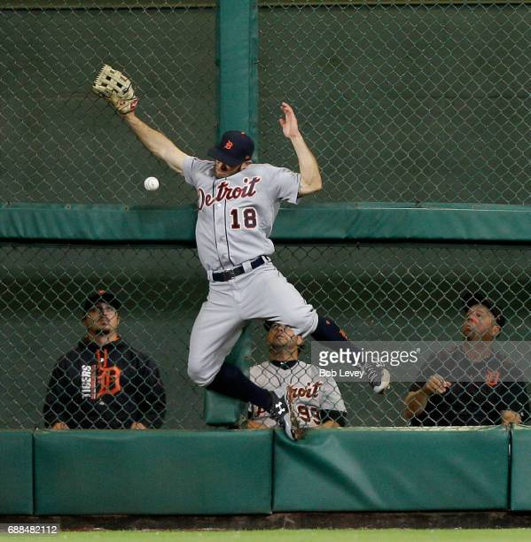Tyler Collins of the Detroit Tigers leaps at the wall but has the ball go off the palm of his glove on a deep fly off the bat of Evan Gattis of the...