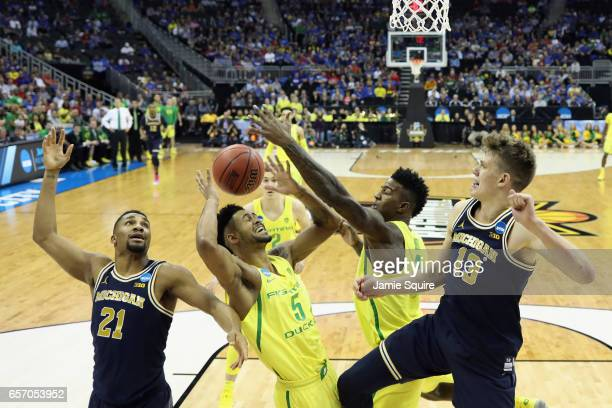 Tyler Dorsey and Jordan Bell of the Oregon Ducks battle for the ball with Zak Irvin and Moritz Wagner of the Michigan Wolverines in the first half...