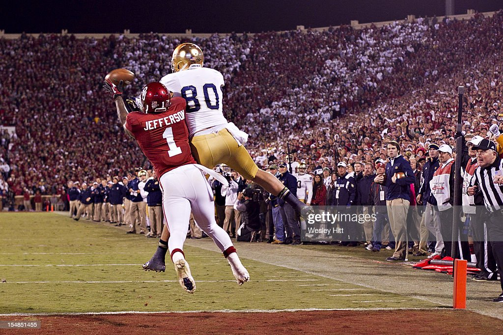 Tyler Eifert #80 of the Notre Dame Fighting Irish catches a pass at the one-yard line in front of Tony Jefferson #1 of the Oklahoma Sooners at Gaylord Family Oklahoma Memorial Stadium on October 27, 2012 in Norman, Oklahoma. The Fighting Irish defeated the Sooners 30-13.