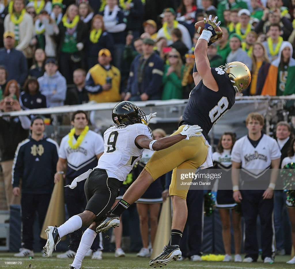 Tyler Eifert #80 of the Notre Dame Fighting Irish catches the ball for a touchdown over Kevin Johnson #9 of the Wake Forest Demon Deacons at Notre Dame Stadium on November 17, 2012 in South Bend, Indiana.