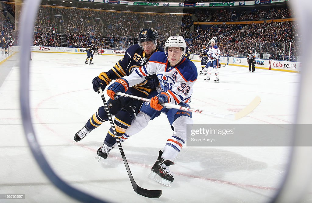 Tyler Ennis #63 of the Buffalo Sabres battles for position along the boards against <a gi-track='captionPersonalityLinkClicked' href=/galleries/search?phrase=Ryan+Nugent-Hopkins&family=editorial&specificpeople=7144190 ng-click='$event.stopPropagation()'>Ryan Nugent-Hopkins</a> #93 of the Edmonton Oilers at First Niagara Center on February 3, 2014 in Buffalo, New York. The Edmonton Oilers defeated the Buffalo Sabres 3-2.