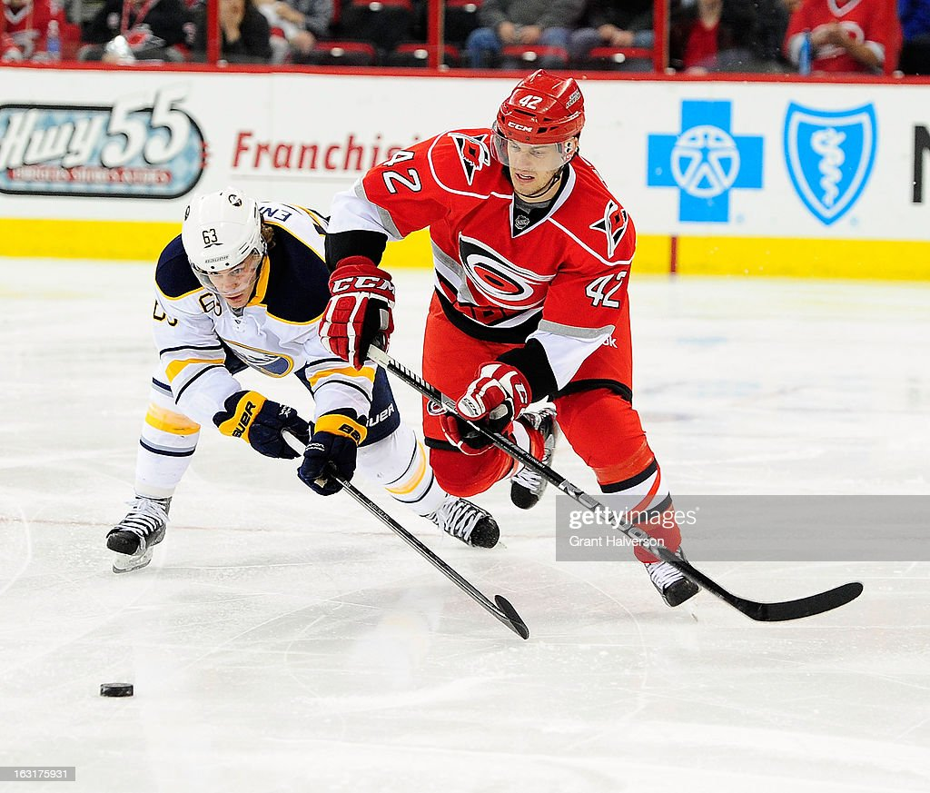 Tyler Ennis #63 of the Buffalo Sabres battles for the puck with Brett Sutter #42 of the Carolina Hurricanes during play at PNC Arena on March 5, 2013 in Raleigh, North Carolina.