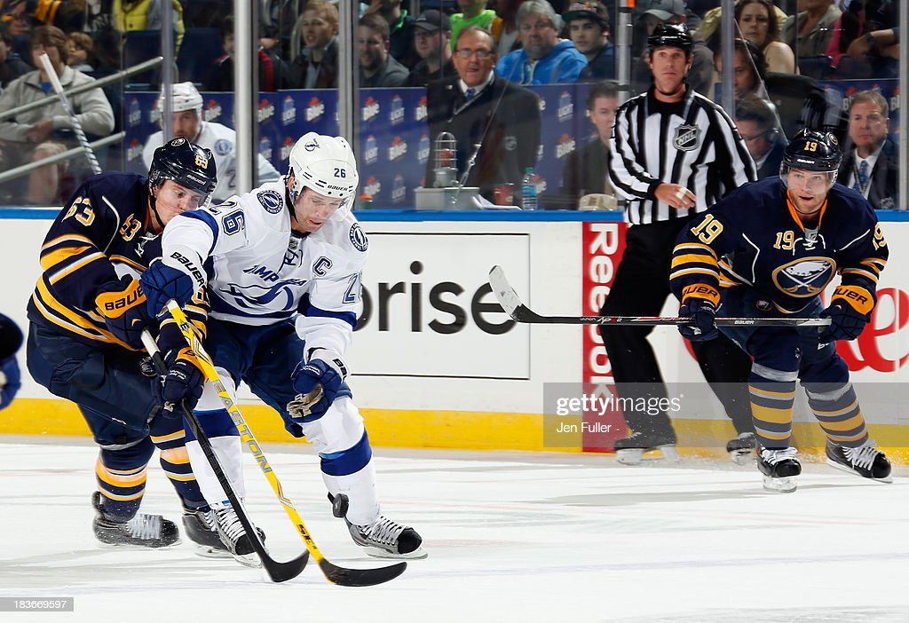 Tyler Ennis #63 of the Buffalo Sabres battles for the puck with Martin St. Louis #26 of the Tampa Bay Lightning as Cody Hodgson #19 of Buffalo skates to follow the play at First Niagara Center on October 8, 2013 in Buffalo, New York.
