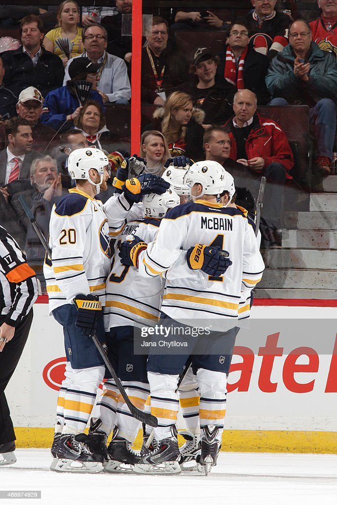 Tyler Ennis #63 of the Buffalo Sabres celebrates his third period goal against the Ottawa Senators with team mates Henrik Tallinder #20 and Jamie McBain #4 during an NHL game at Canadian Tire Centre on February 6, 2014 in Ottawa, Ontario, Canada.