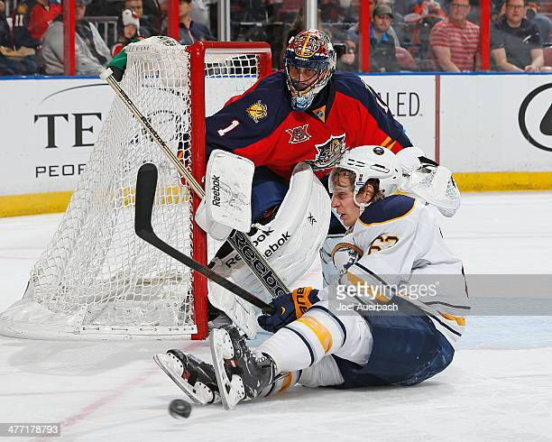 Tyler Ennis of the Buffalo Sabres is cross checked by Erik Gudbranson in front of Roberto Luongo#1 of the Florida Panthers at the BBT Center on March...