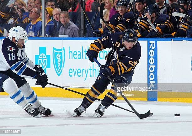 Tyler Ennis of the Buffalo Sabres is stick checked by Andrew Ladd of the Winnipeg Jets on April 22 2013 at the First Niagara Center in Buffalo New...