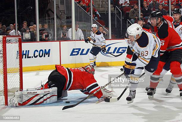 Tyler Ennis of the Buffalo Sabres is stopped by Johan Hedberg of the New Jersey Devils at the Prudential Center on November 10 2010 in Newark New...