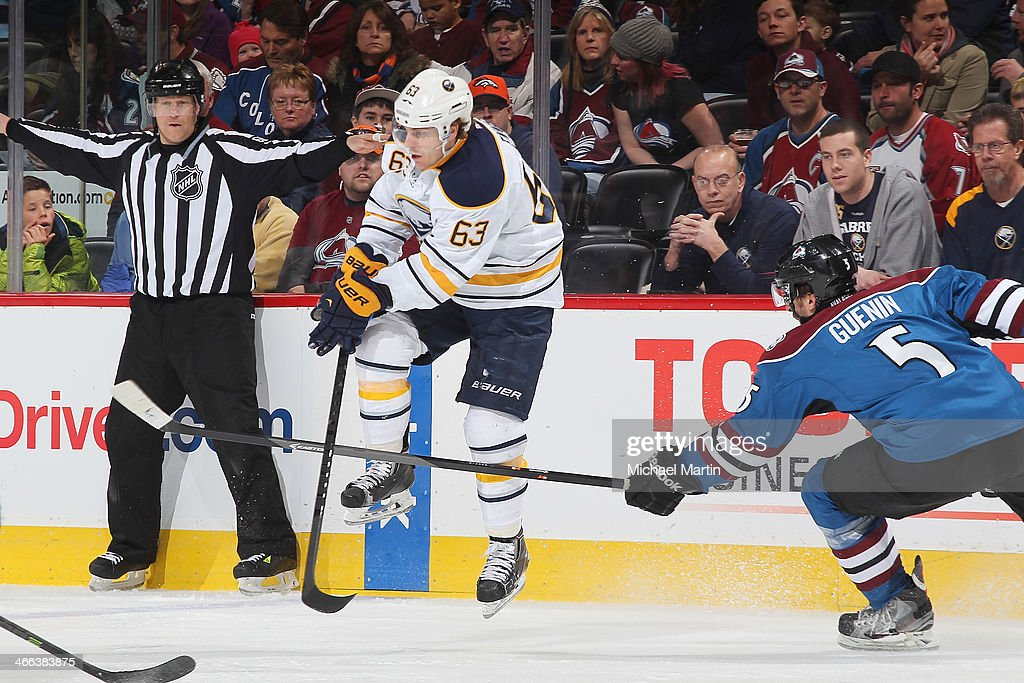 Tyler Ennis #63 of the Buffalo Sabres jumps to avoid pressure by <a gi-track='captionPersonalityLinkClicked' href=/galleries/search?phrase=Nate+Guenin&family=editorial&specificpeople=3948510 ng-click='$event.stopPropagation()'>Nate Guenin</a> #5 of the Colorado Avalanche at the Pepsi Center on February 1, 2014 in Denver, Colorado.