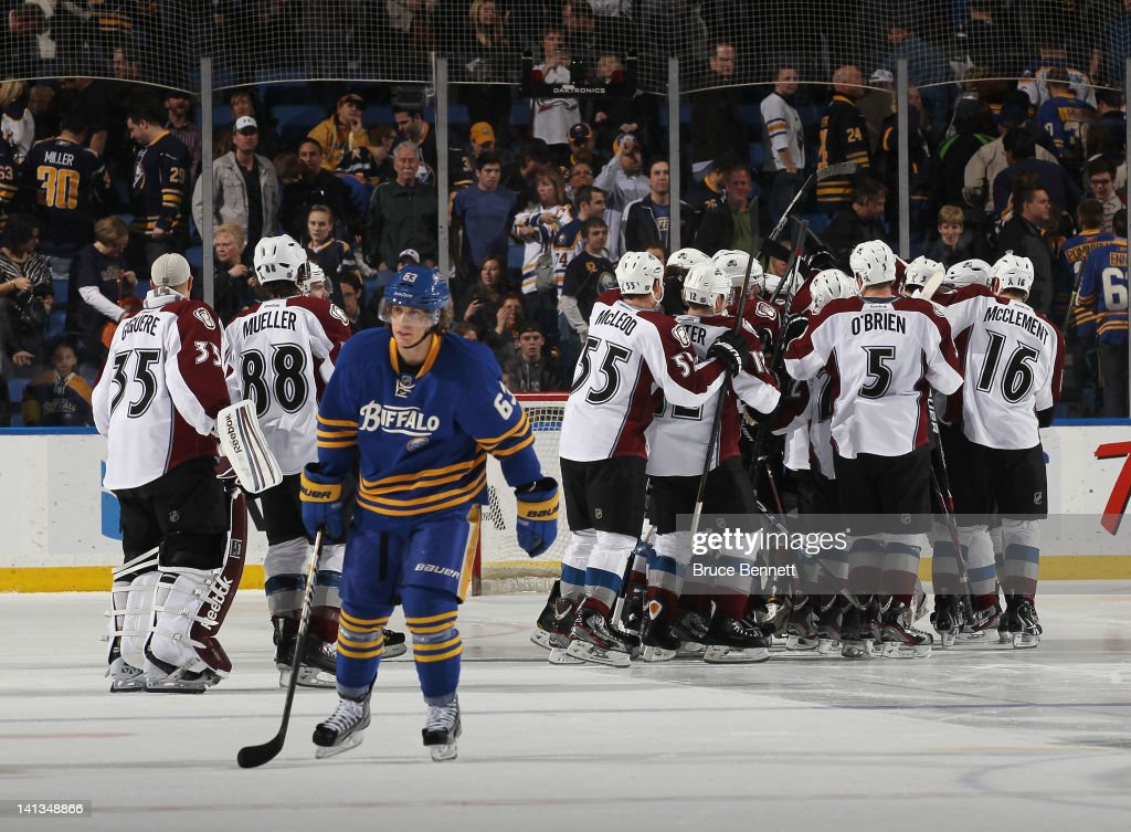 Tyler Ennis #63 of the Buffalo Sabres leaves the ice after failing to score in the shootout against the Colorado Avalanche who celebrate their victory at the First Niagara Center on March 14, 2012 in Buffalo, New York. The Avalanche defeated the Sabres 4-3 in the shootout.