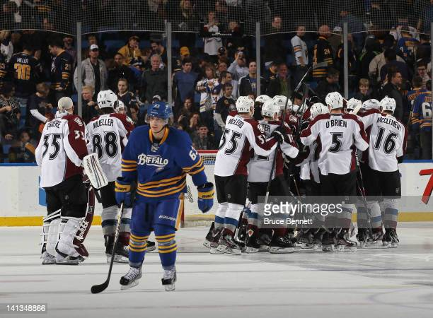 Tyler Ennis of the Buffalo Sabres leaves the ice after failing to score in the shootout against the Colorado Avalanche who celebrate their victory at...