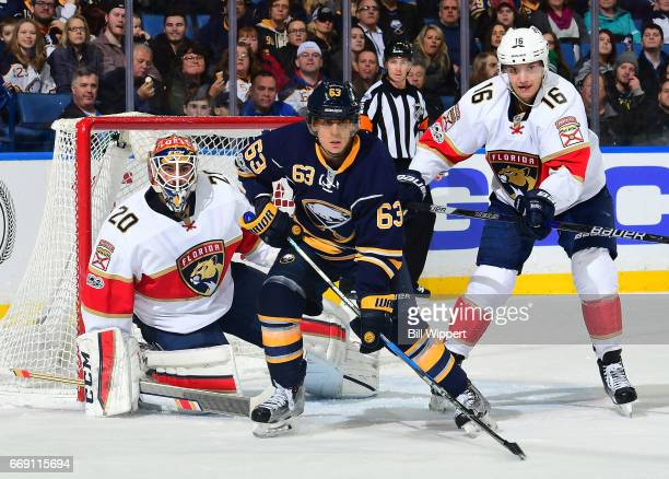 Tyler Ennis of the Buffalo Sabres skates between Reto Berra and Aleksander Barkov of the Florida Panthers during an NHL game at the KeyBank Center on...