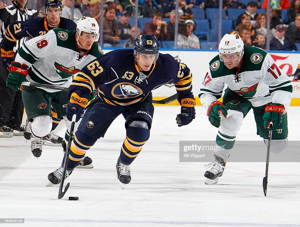 <a gi-track='captionPersonalityLinkClicked' href=/galleries/search?phrase=Tyler+Ennis+-+Ice+Hockey+Player&family=editorial&specificpeople=4754184 ng-click='$event.stopPropagation()'>Tyler Ennis</a> #63 of the Buffalo Sabres skates with the puck against <a gi-track='captionPersonalityLinkClicked' href=/galleries/search?phrase=Stephane+Veilleux&family=editorial&specificpeople=217366 ng-click='$event.stopPropagation()'>Stephane Veilleux</a> #19 and <a gi-track='captionPersonalityLinkClicked' href=/galleries/search?phrase=Torrey+Mitchell&family=editorial&specificpeople=4504539 ng-click='$event.stopPropagation()'>Torrey Mitchell</a> #17 of the Minnesota Wild on October 14, 2013 at the First Niagara Center in Buffalo, New York. Minnesota won, 2-1.