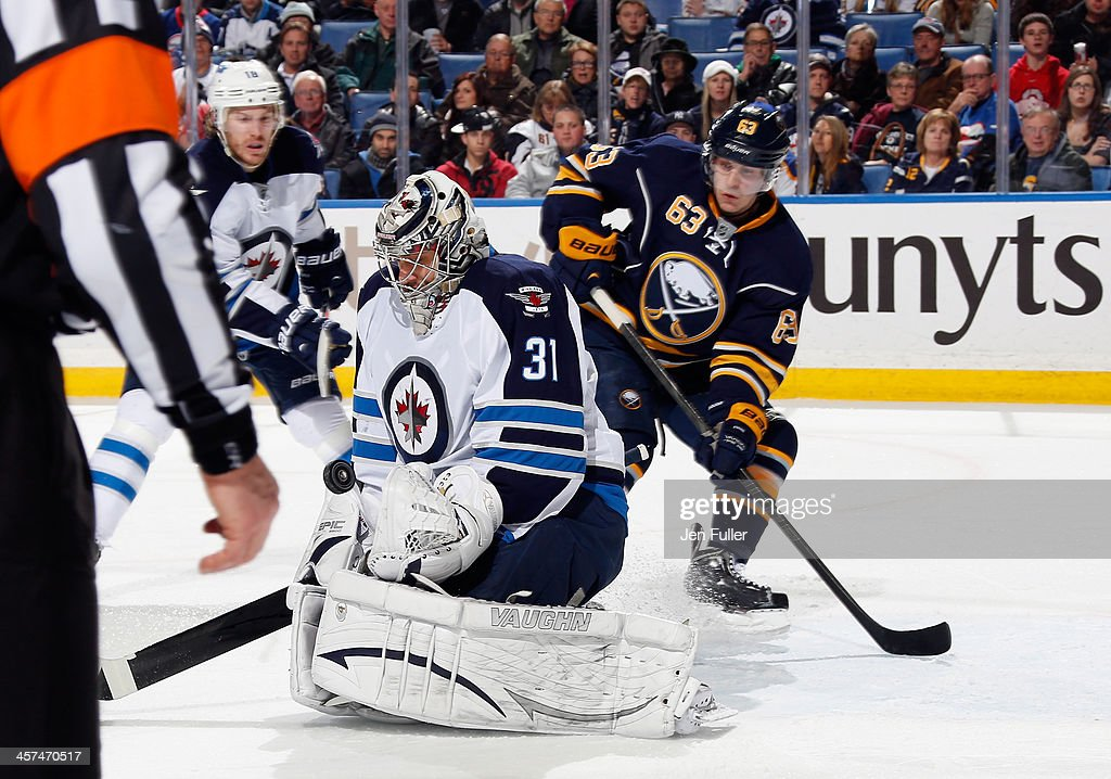 Tyler Ennis #63 of the Buffalo Sabres waits for a rebound as Ondrej Pavelec #31 of the Winnipeg Jets blocks a shot on goal at First Niagara Center on December 17, 2013 in Buffalo, New York. Buffalo defeated Winnipeg 4-2.